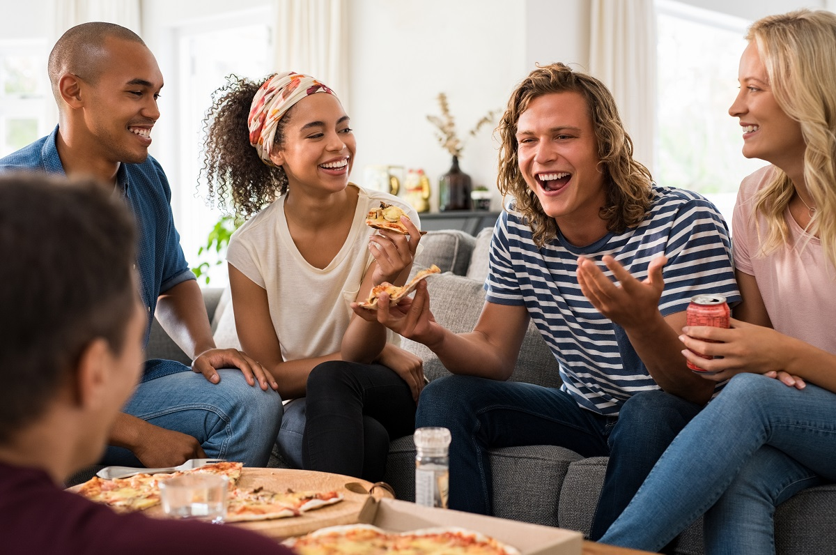 Friends eating pizza in the living room