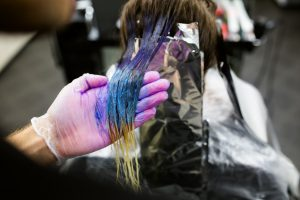 Woman's hair being dyed with blue