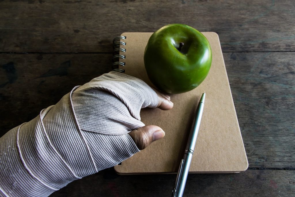 Fractured hand beside a notebook and apple