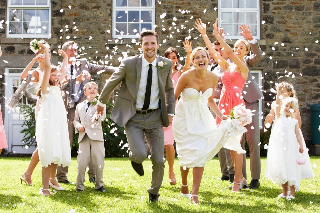 Guests throwing confetti over the newly weds