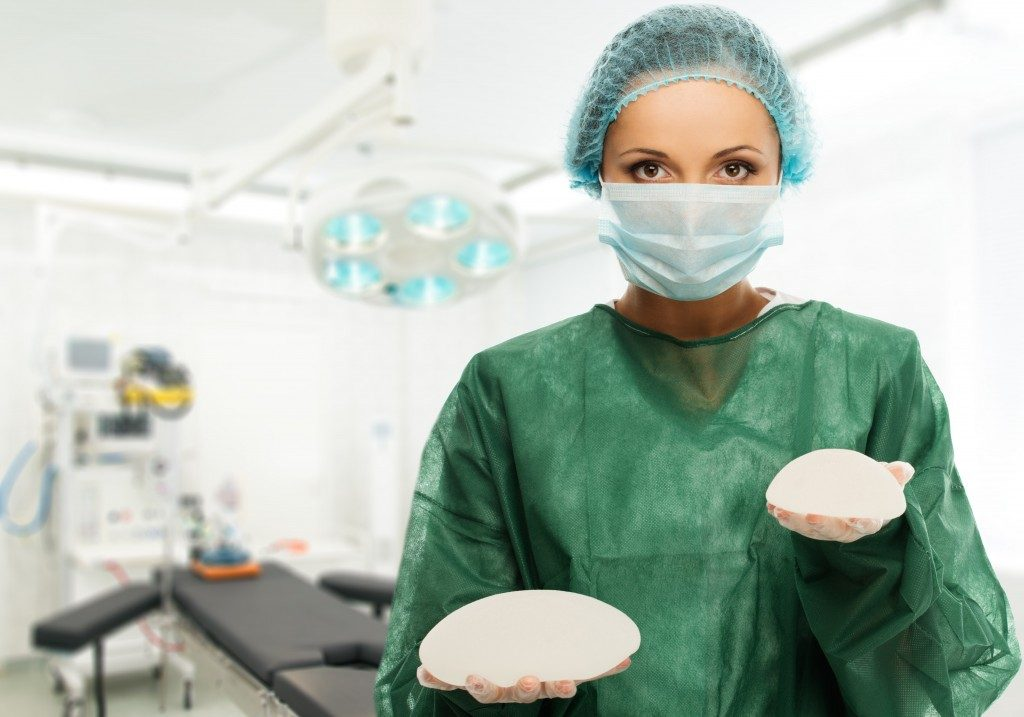 Surgeon holding silicon breast implants