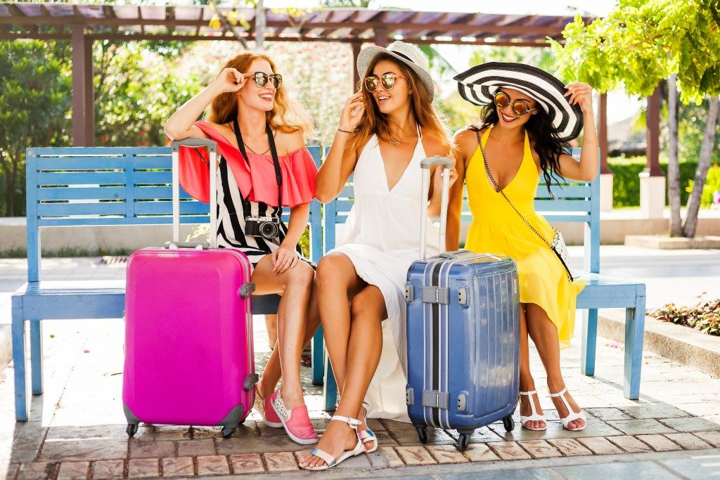 Three beautiful fashion girls sitting with their suitcases and wait in the terminal at the airport.