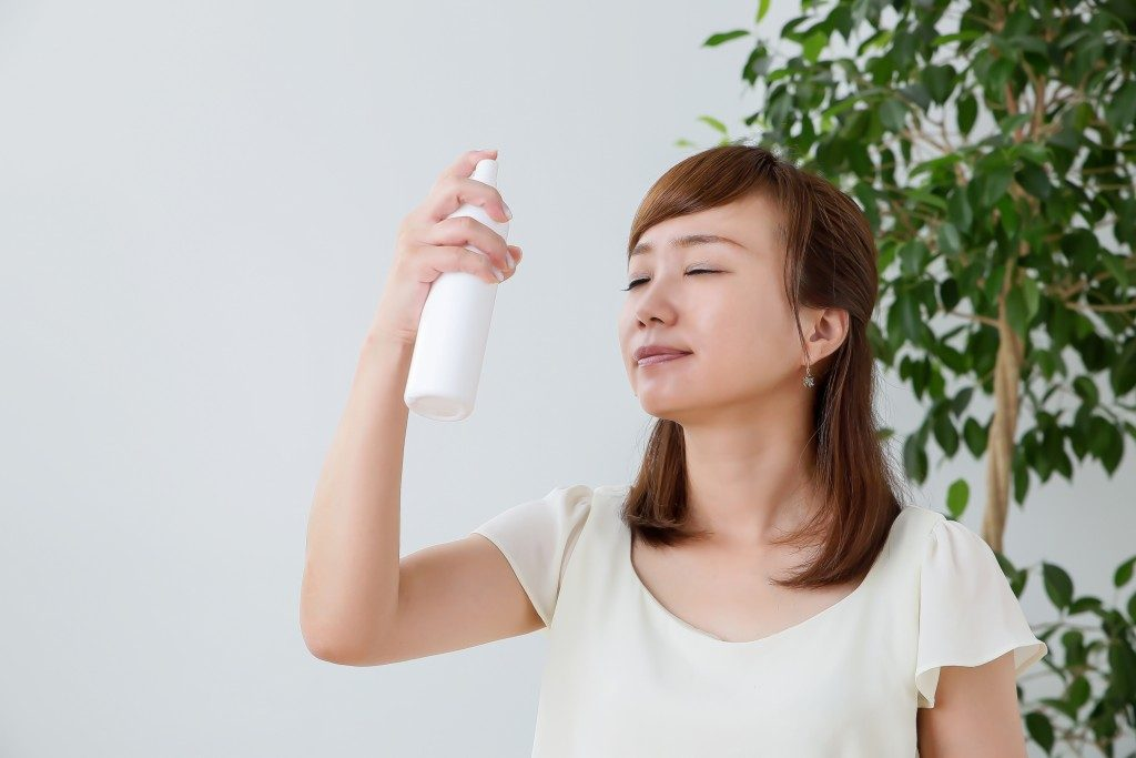 woman spraying facial mist