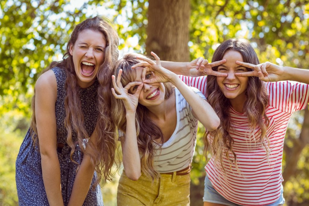 three young women smiling and being playful