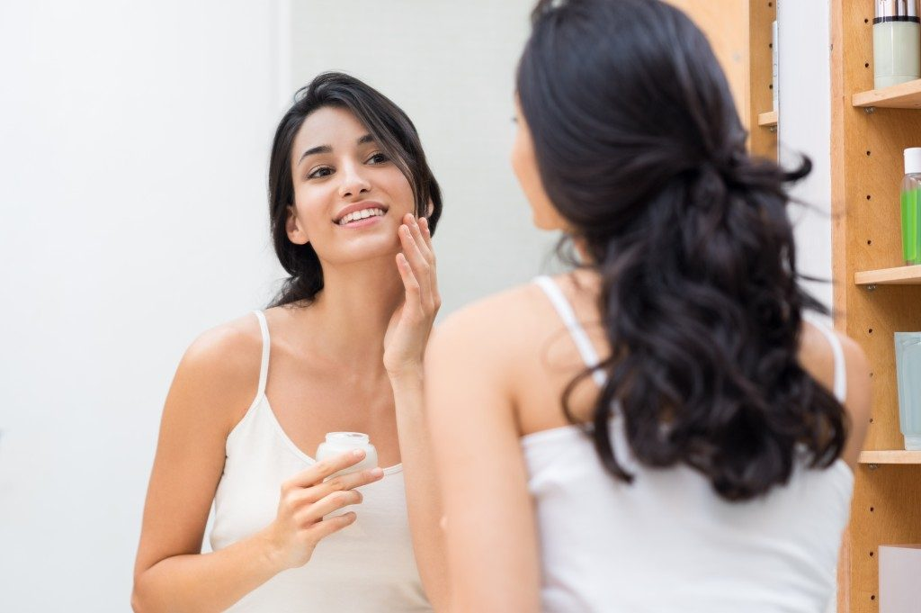 Woman caring of her beautiful skin on the face standing near mirror in the bathroom.