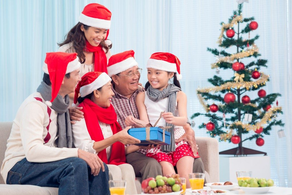 Family wearing Christmas hats and exchanging gifts