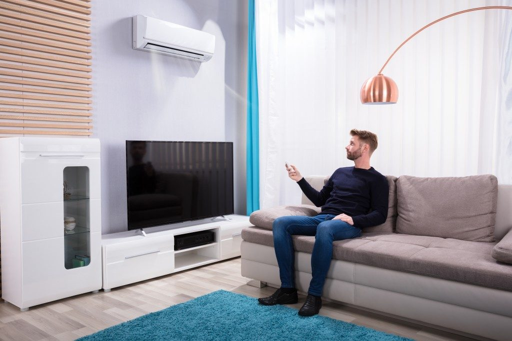 man turning on his air condition unit with remote