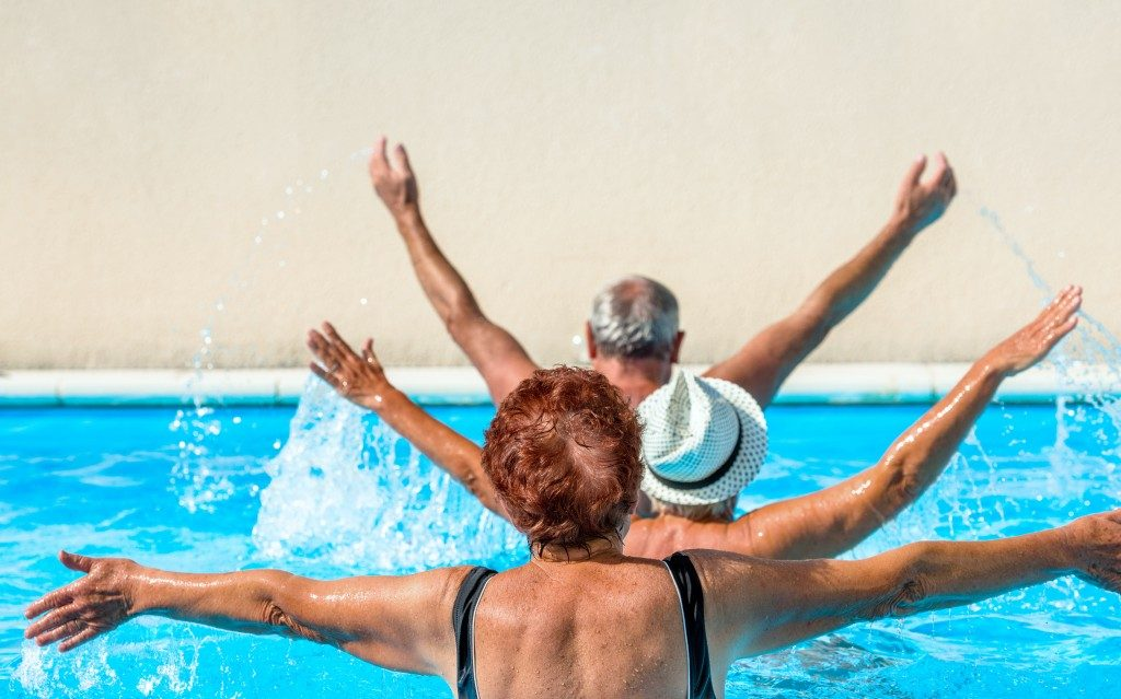 aged group doing water aerobics in a swimming pool