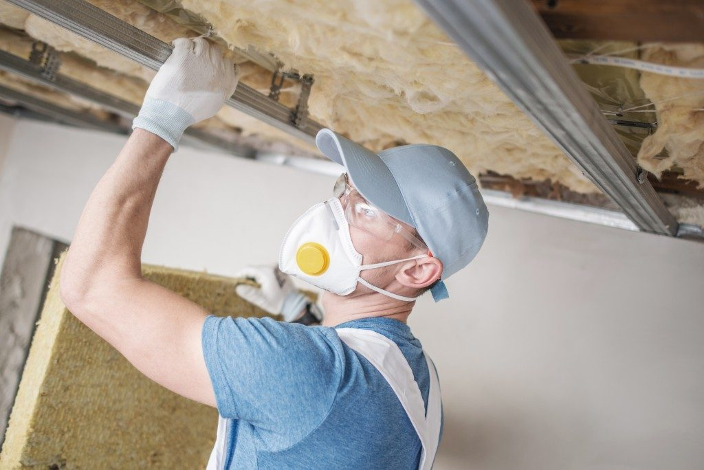Worker insulating a house