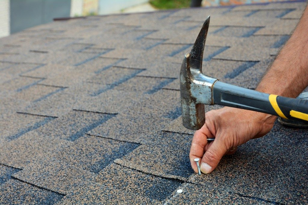 using hammer and nail on roof shingles