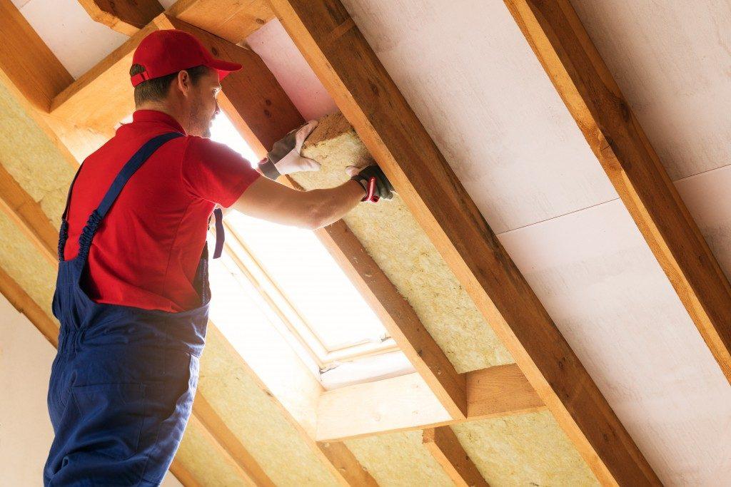 Construction worker installing insulation