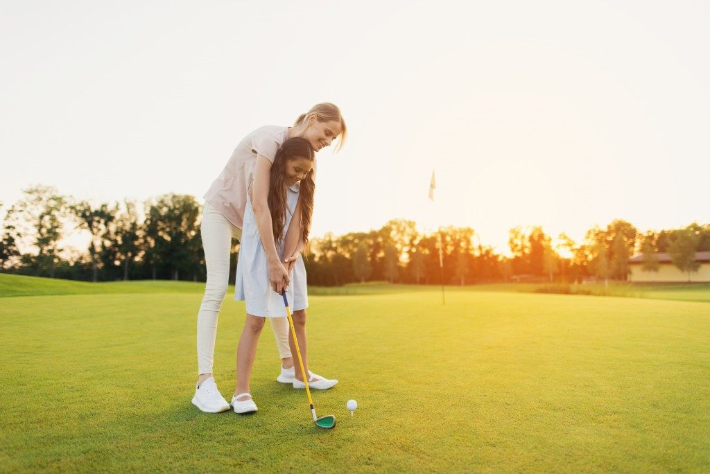 girl playing golf with her mom