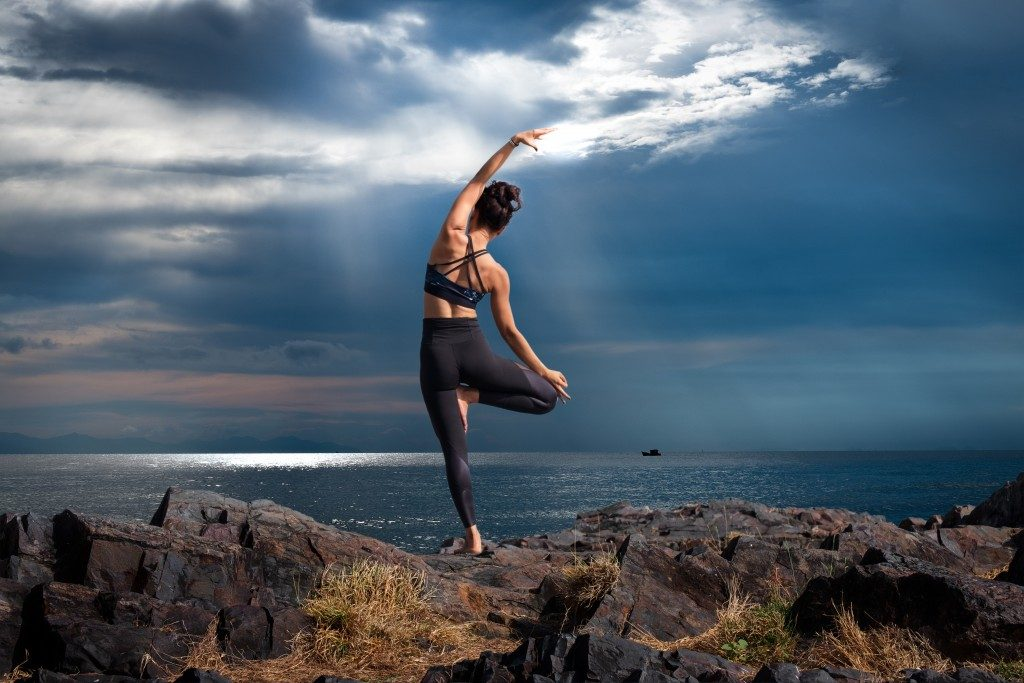 woman stretching on a hill
