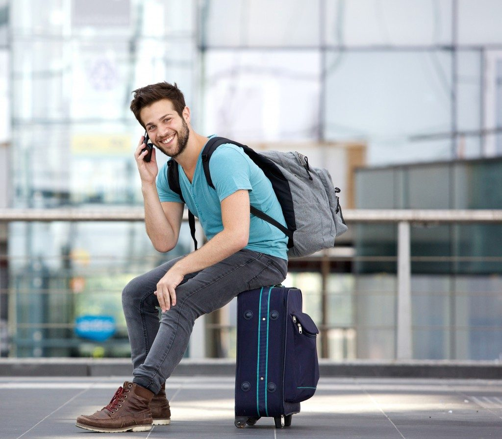 Portrait of a handsome young man sitting on suitcase and calling by cellphone at airport