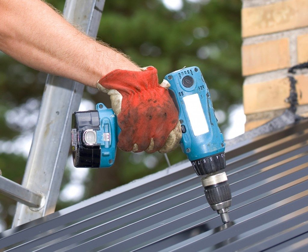 man working with a power drill on a roof
