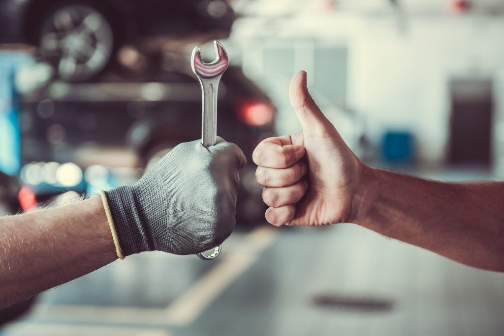 repairman with wrench and customer giving thumbsup