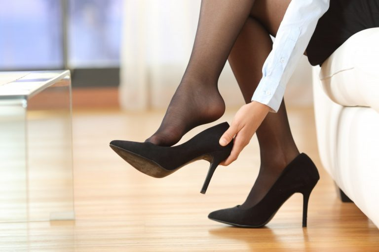 Businesswoman taking off high heels shoes after work at home
