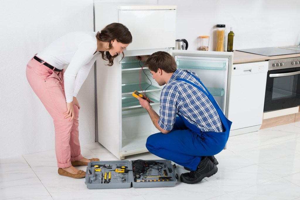Beautiful Housewife Looking At Male Worker Repairing Refrigerator In Kitchen Room