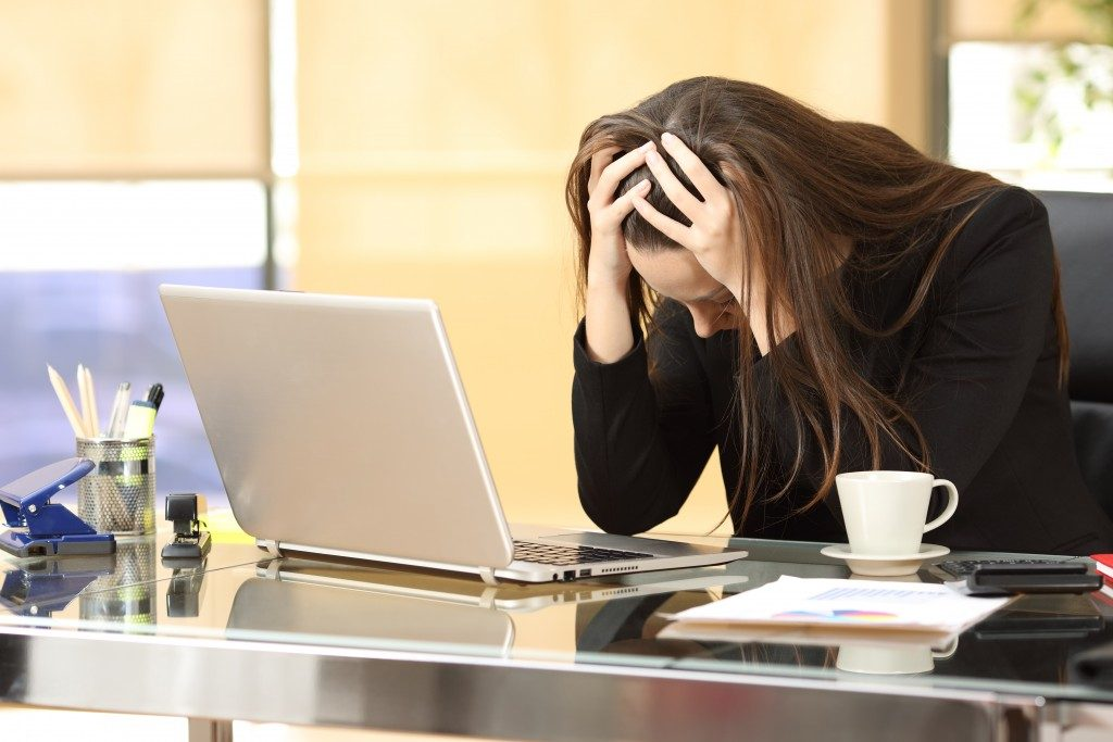 upset employee sitting in front of a laptop