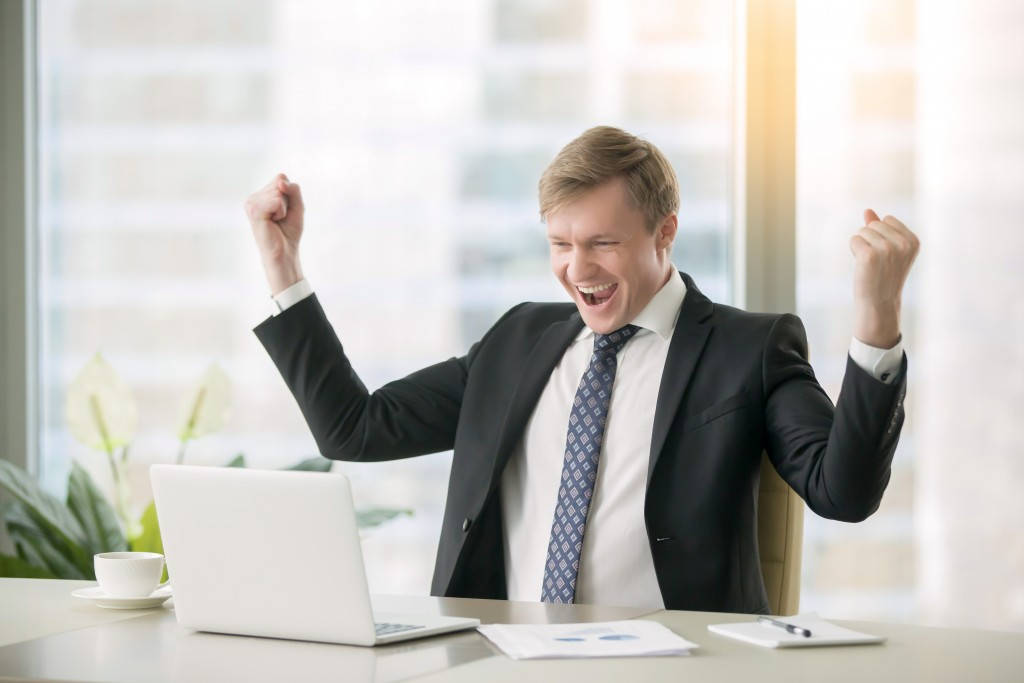 Businessman celebrating a win while looking at the laptop