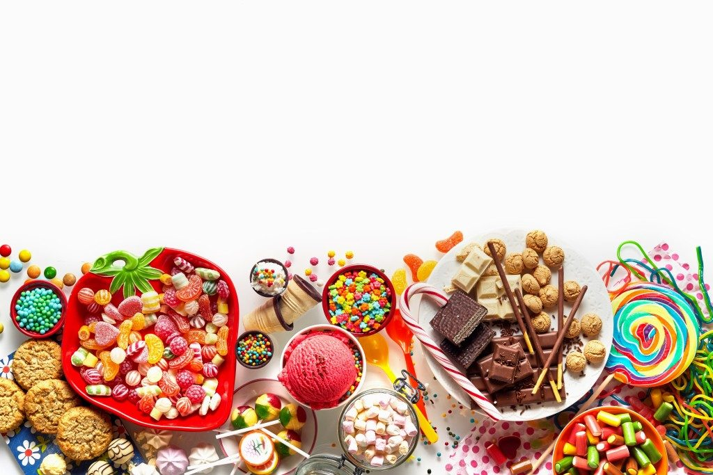 Large colorful selection of kids party food and sweets with cookies, ice cream, lollipops and candy