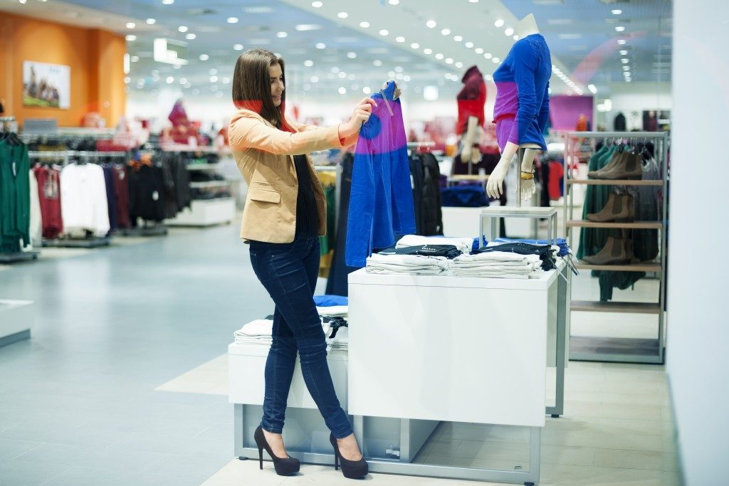 Woman looking at a blue blouse in shopping center