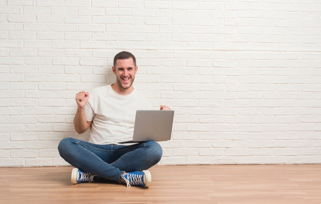 Man celebrating while having his laptop
