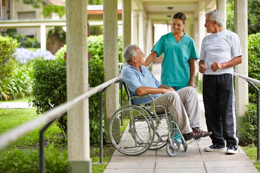 senior citizens talking to a nurse in a hospital garden