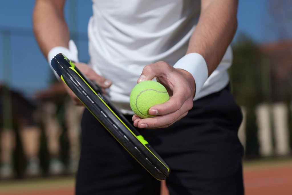 tennis player holding a ball and racket