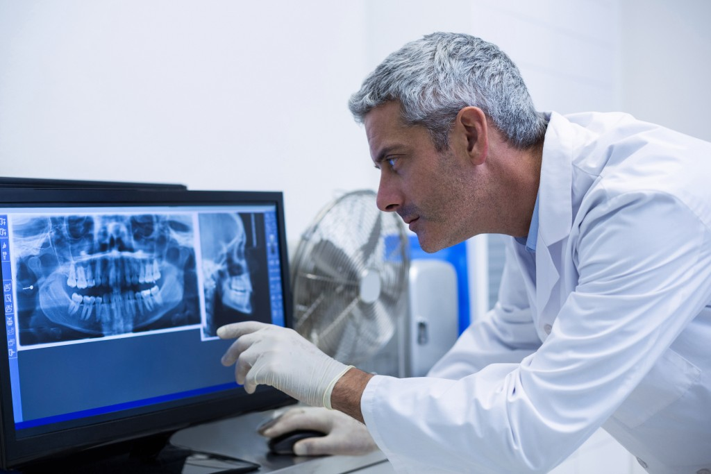 dentist examining an x-ray on the monitor in clinic