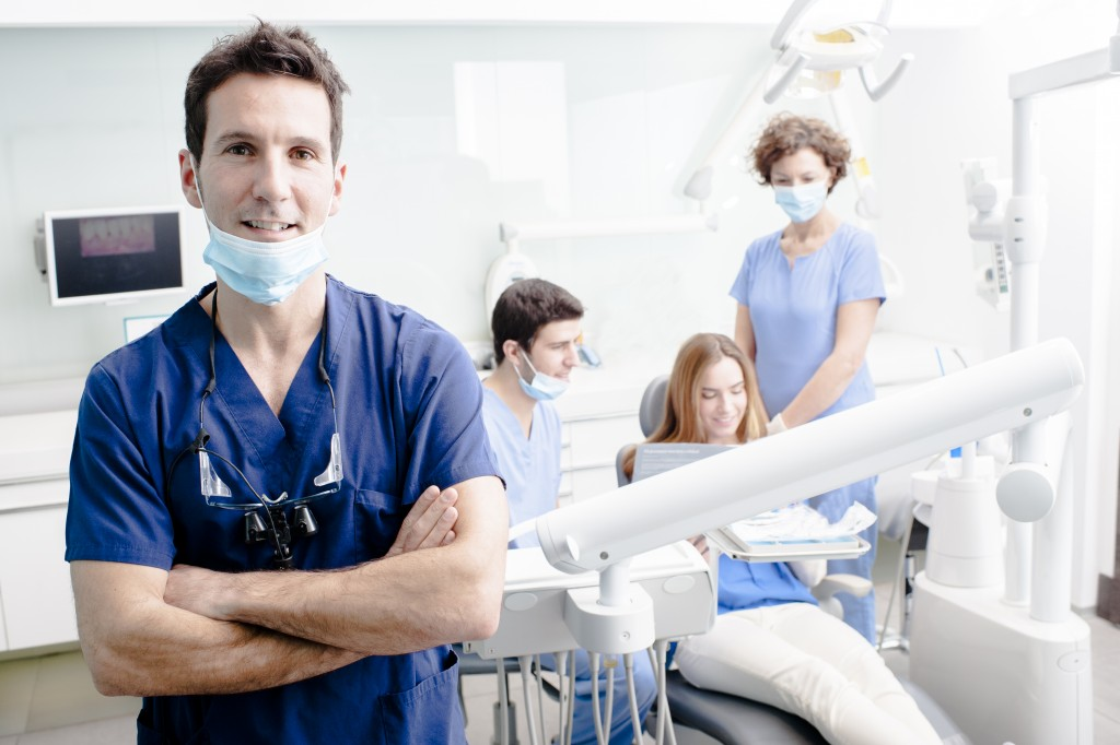 dentist with his team working in the background