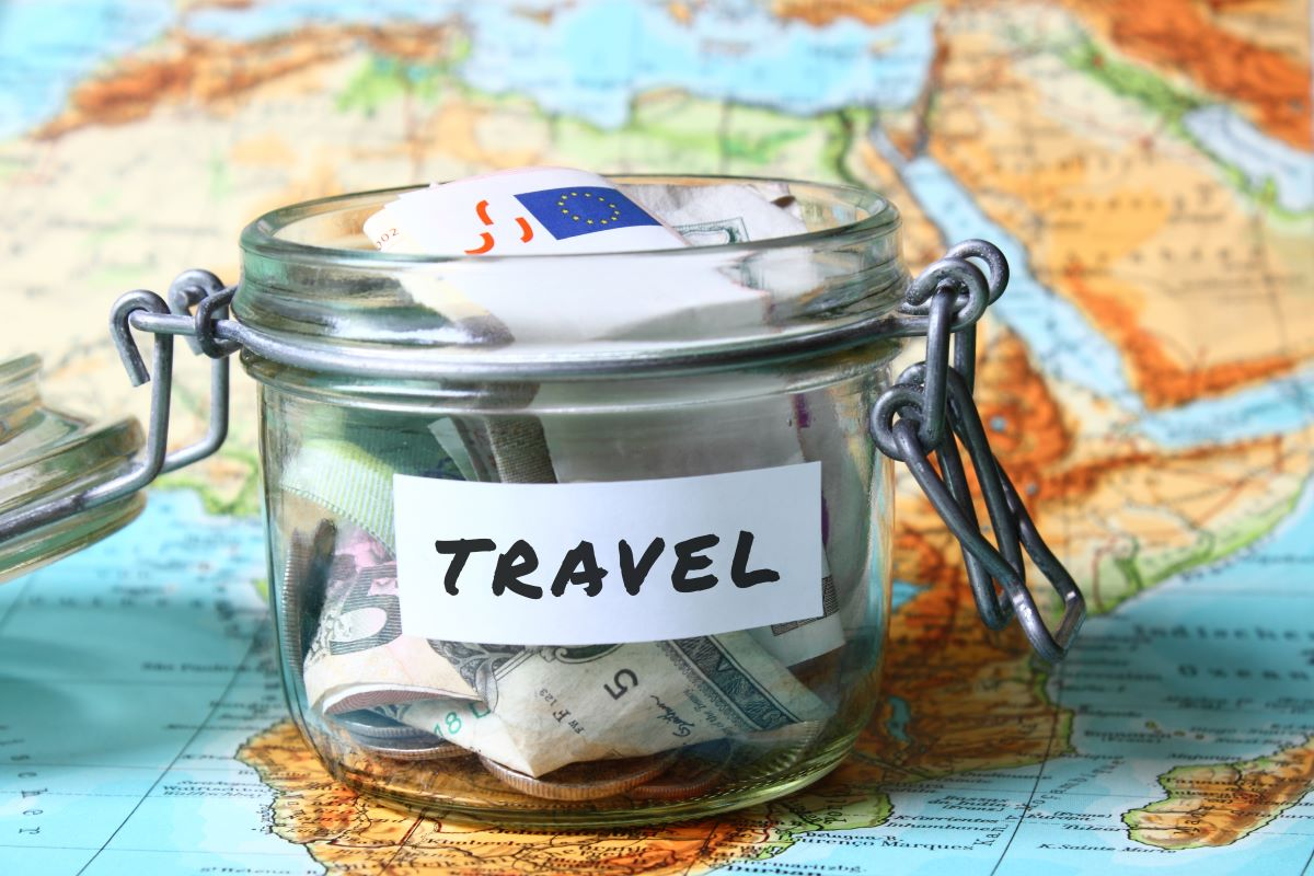 jar labeled as travel full of savings on top of a world map
