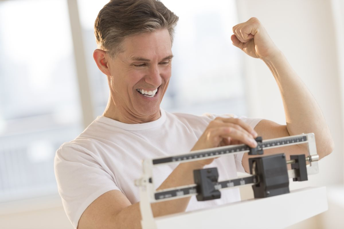 man smiling on weighing scale