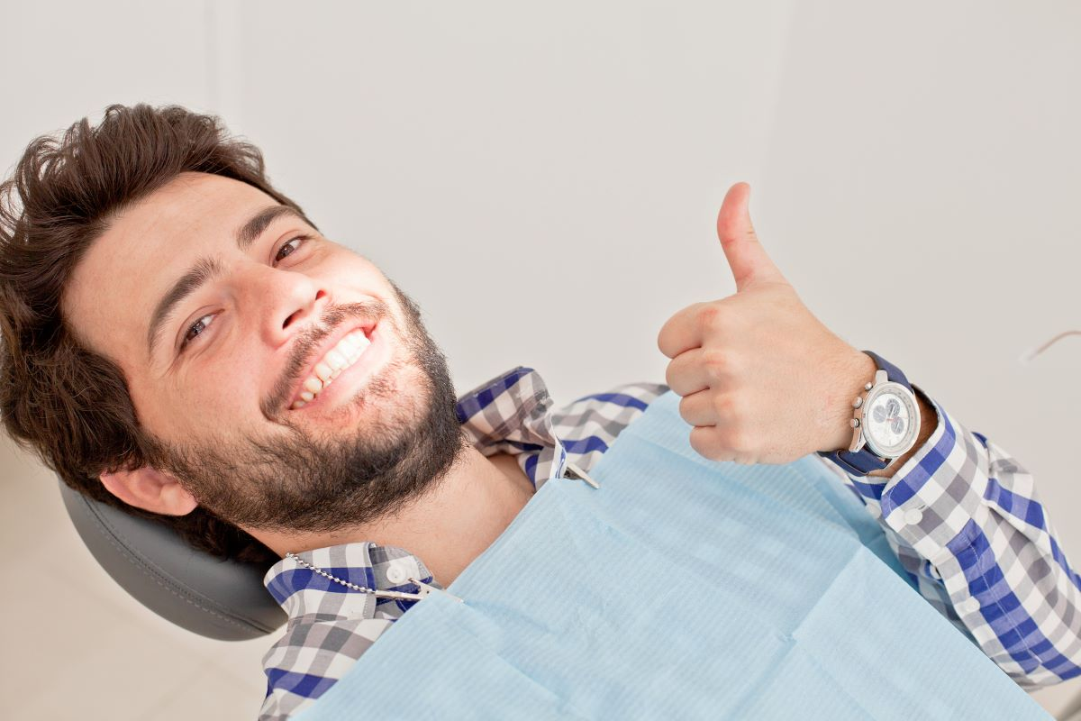 man at the dentists smiling thumbs up