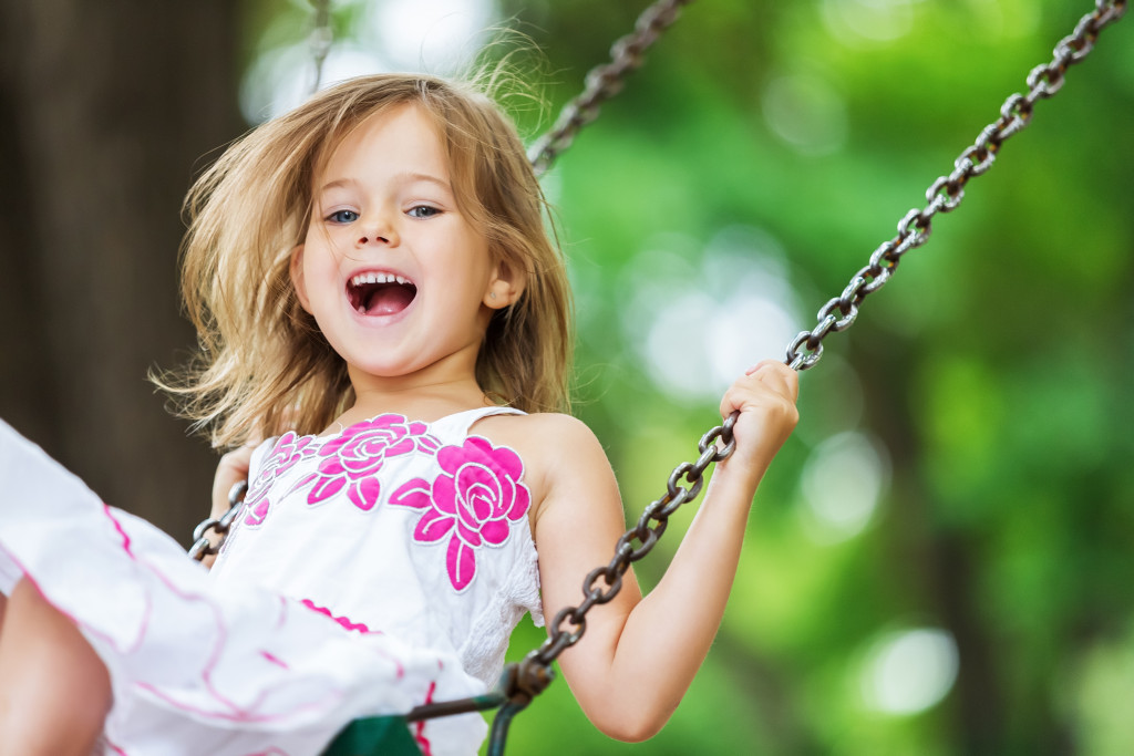 little girl playing at a swing