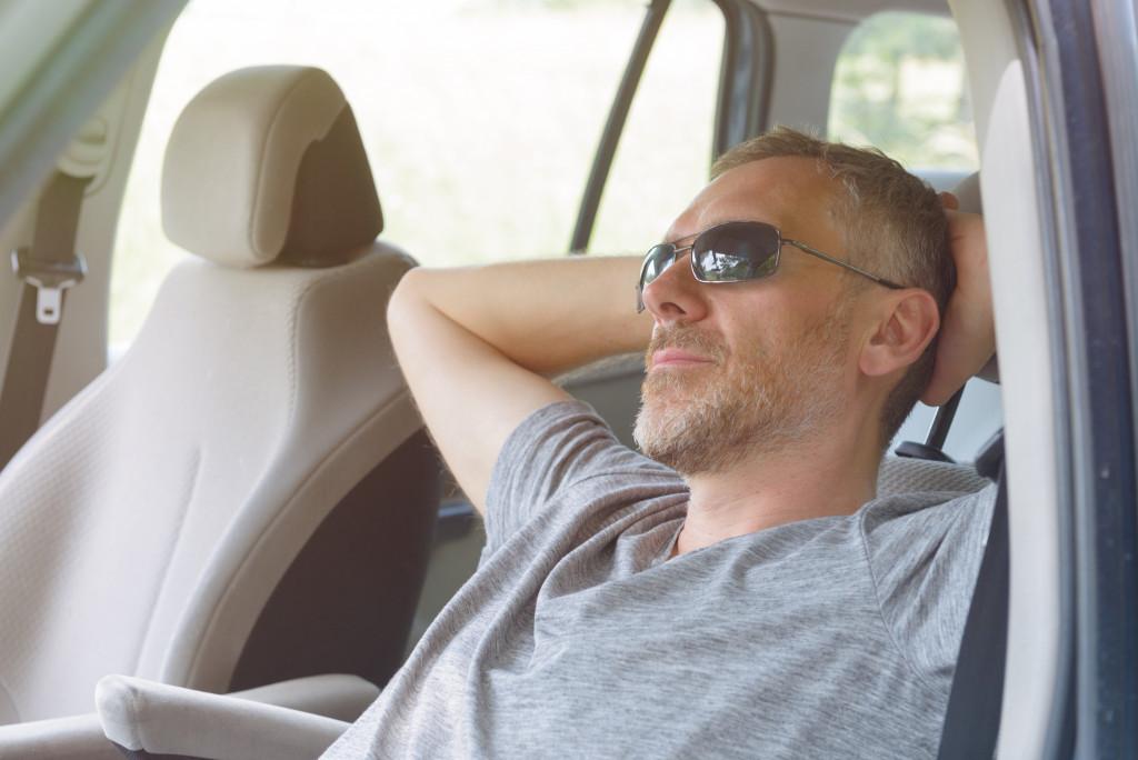 man relaxing in car
